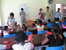 단기 자원봉사자가 매니저의 도움을 받아 종이접기 교실을 진행 하는 모습